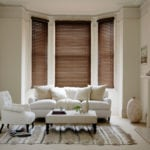 walnut wooden venetian window blinds in a bay window of a living room