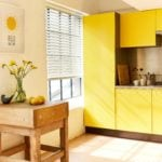 ivory white venetian window blind covering a window in a modern kitchen with bright yellow cabinets