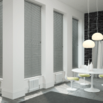 grey venetian window blinds covering multiple large floor to ceiling windows in a modern dining room