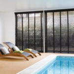 black wooden venetian window blinds covering large windows in front of an indoor swimming pool