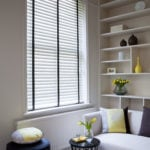 polar white venetian window blinds with contrasting black tapes covering a window in a modern living room
