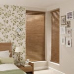 medium oak venetian window blinds covering a window in a bedroom