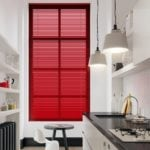 bold red venetian window blinds covering a large vertical window in a modern white kitchen