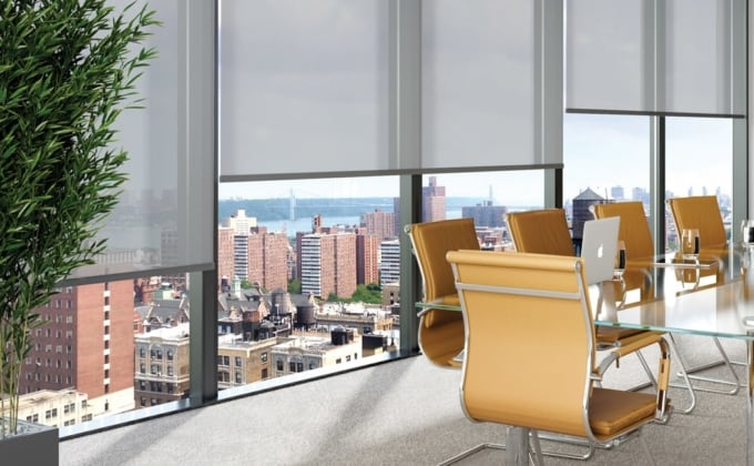 sheer light grey roller window blinds covering the large floor to ceiling windows of a modern meeting room in a city office building