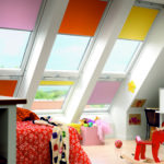 brightly primary coloured velux window blinds in a children loft playroom